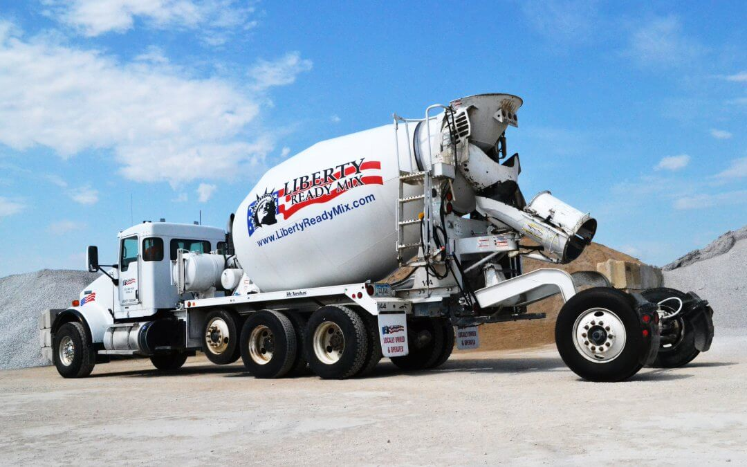 A white Liberty Ready Mix cement mixers in front of piles of recycled concrete.