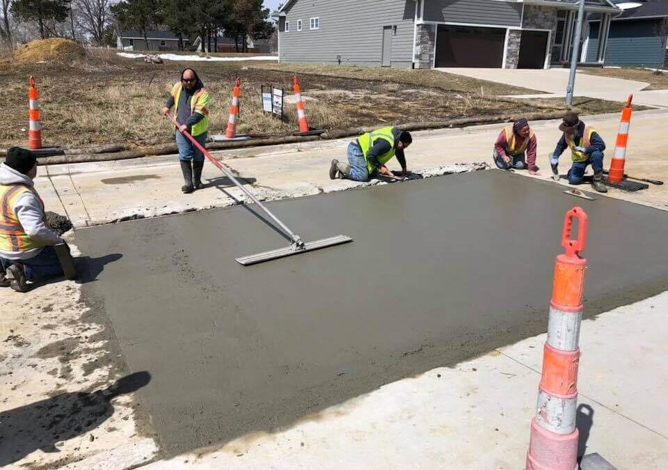 One man is using a tool to flatten a wet concrete slab while four other workers in safety vests are positioned at the sides of the slab.