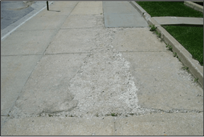 A cement slab that contains cracks and erosion.