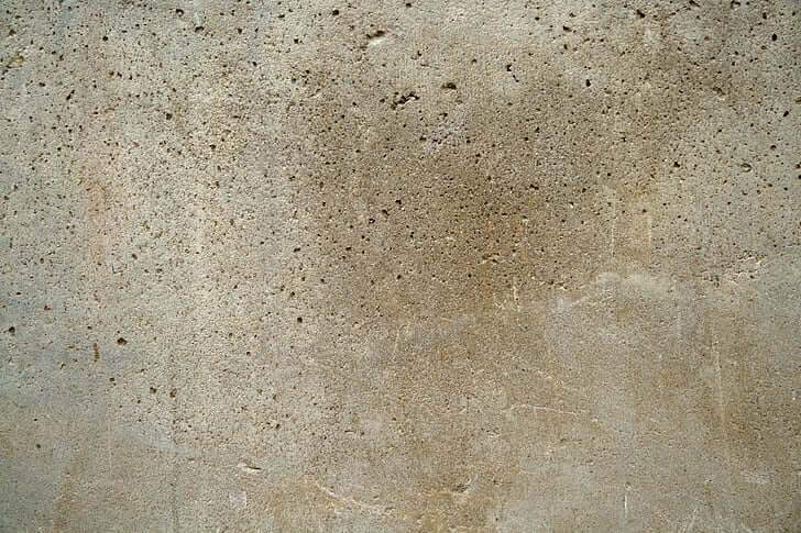 A close-up picture of a concrete wall with some pockets and holes.