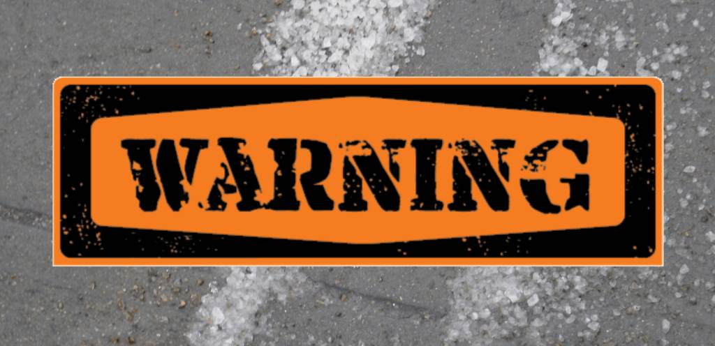 An orange rectangle that says WARNING in large black letters.is placed over a slab of sidewalk concrete with ice melter spread on it