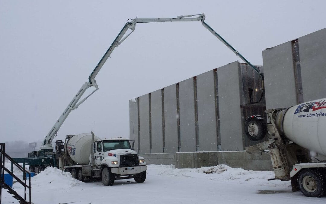 Two white Liberty Ready Mix concrete trucks are parked and pumping concrete in the middle of a snow during winter.