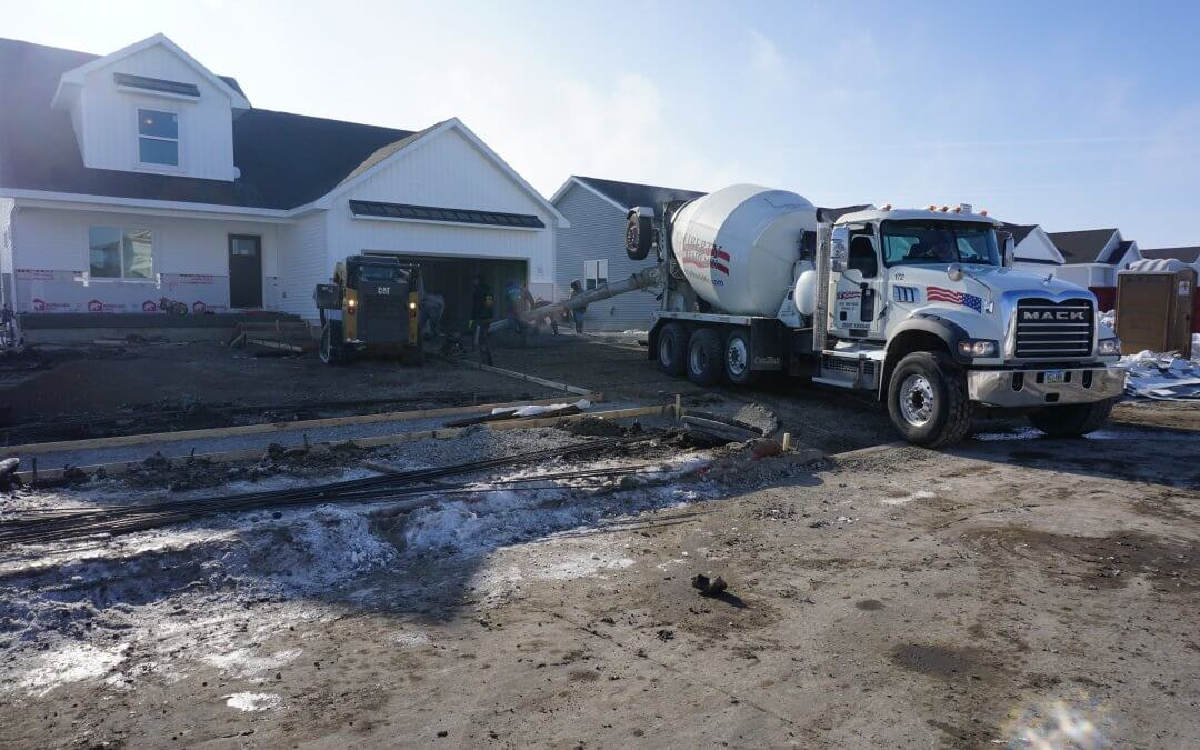 A Liberty Ready Mix cement mixer lined up to pour concrete for a residential driveway and sidewalk.