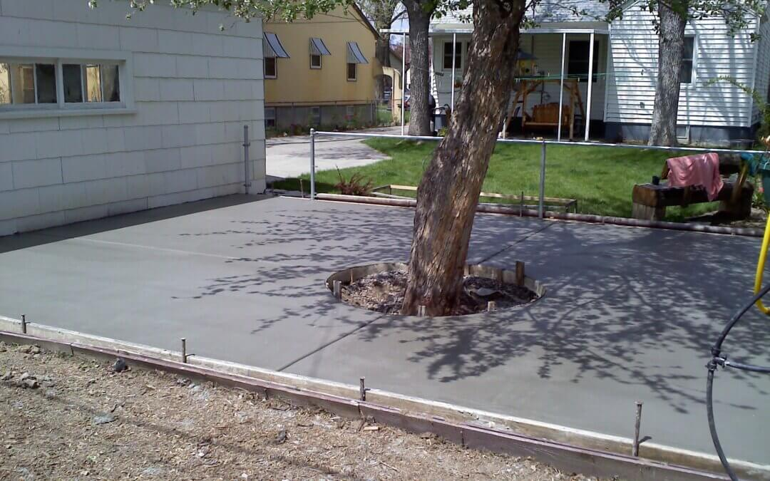 A new DIY concrete patio is poured and curing.